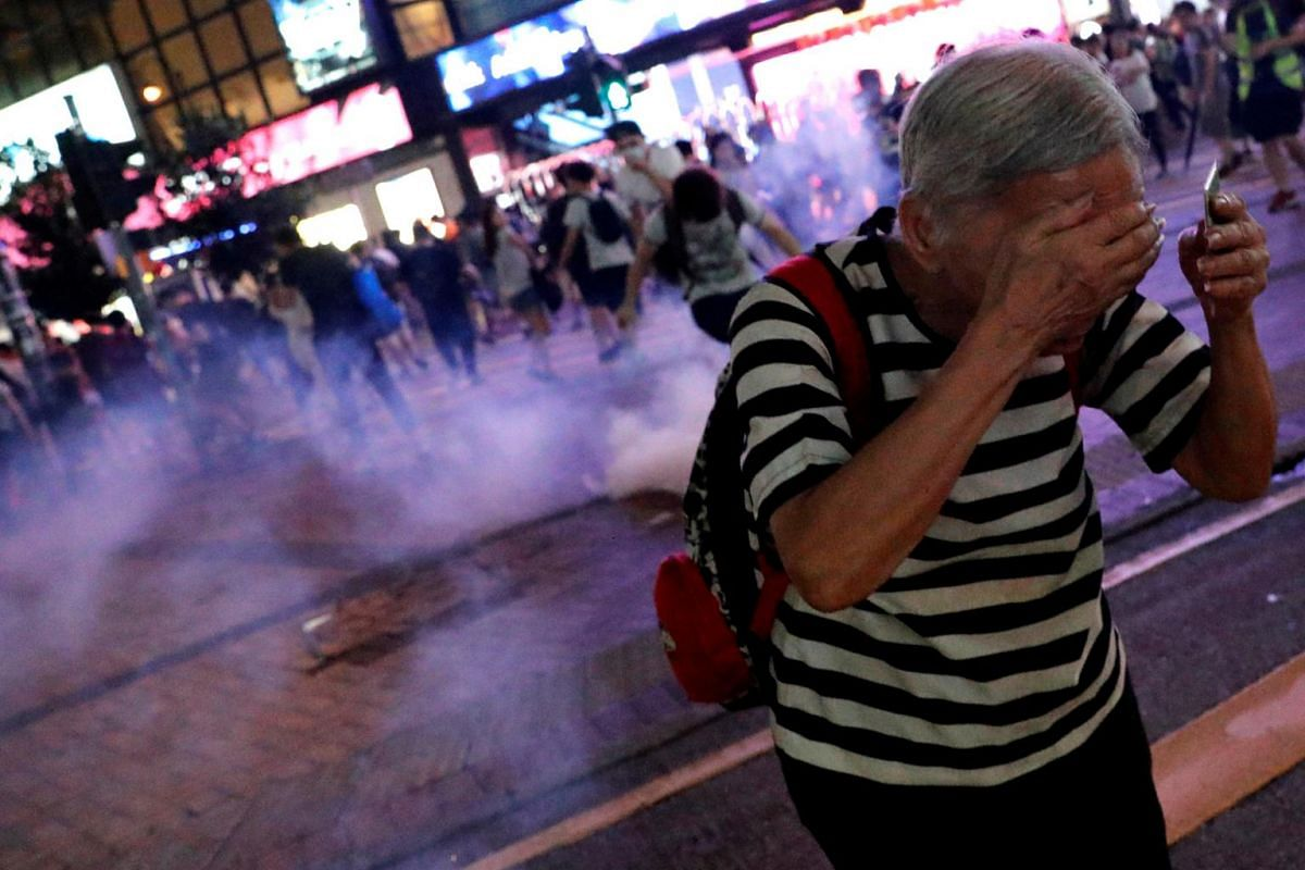 A woman runs away from tear gas after a march to call for the passing of the proposed Hong Kong Human Rights and Democracy Act by the US Congress, in Hong Kong, on Sept 8, 2019.