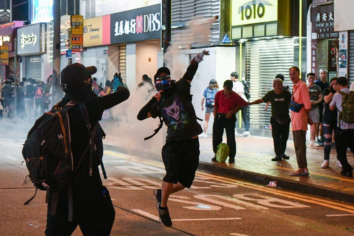 A protester tosses back a tear gas canister fired by riot police in Causeway Bay in Hong Kong, on Sept 8, 2019.