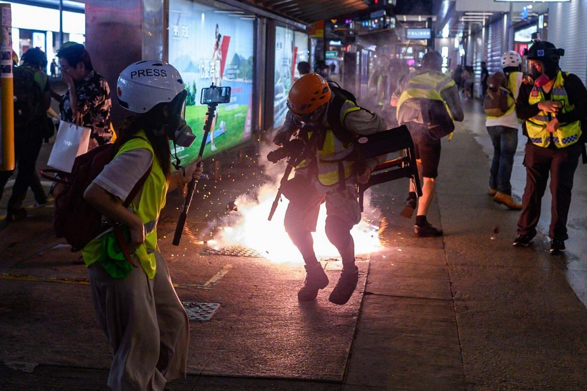 People and journalists react as police fire tear gas from Causeway Bay MTR station during clashes with pro-democracy demonstrators in Hong Kong, on Sept 8, 2019.