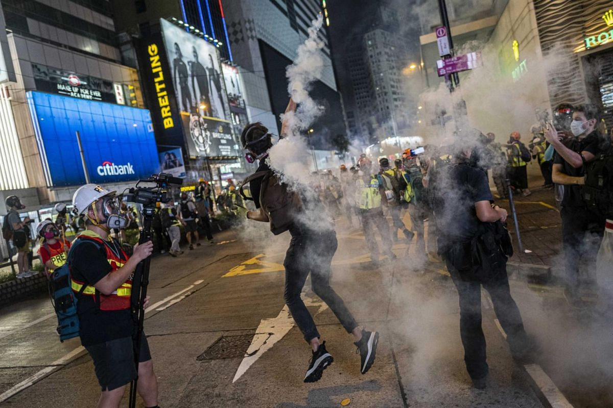 A protester throws a tear gas canister during clashes with police in Hong Kong, on Sept 8, 2019.
