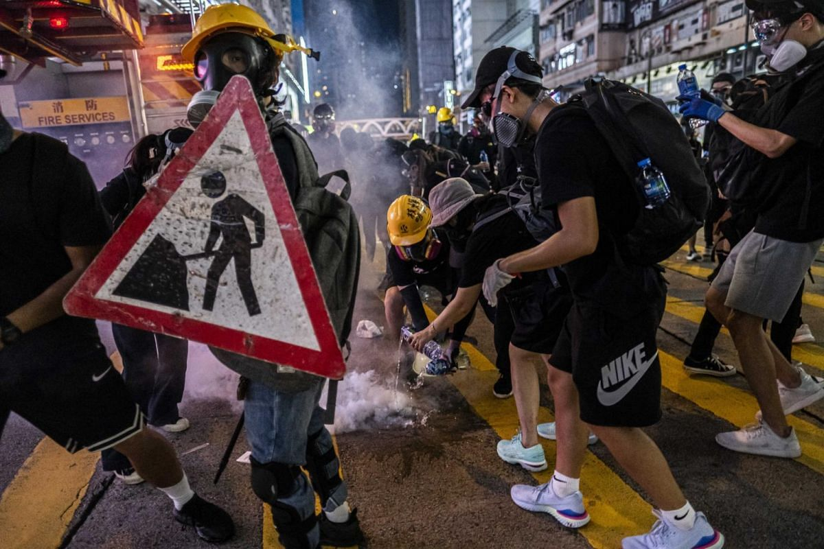 Protesters douse a tear gas canister during clashes with police in Hong Kong, on Sept 8, 2019.