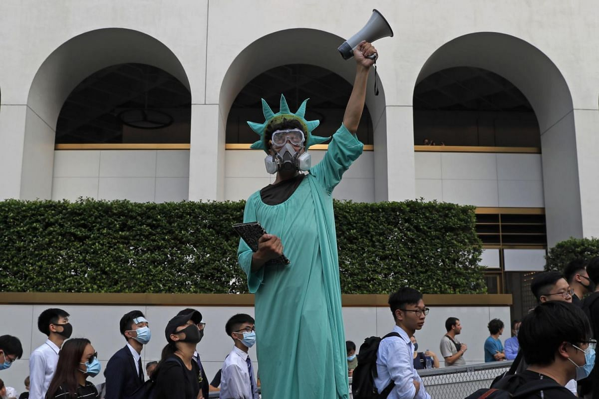 A protester dressed as the Statue of Liberty poses as people march past from Chater Garden to the US Consulate in Hong Kong, on Sept 8, 2019.