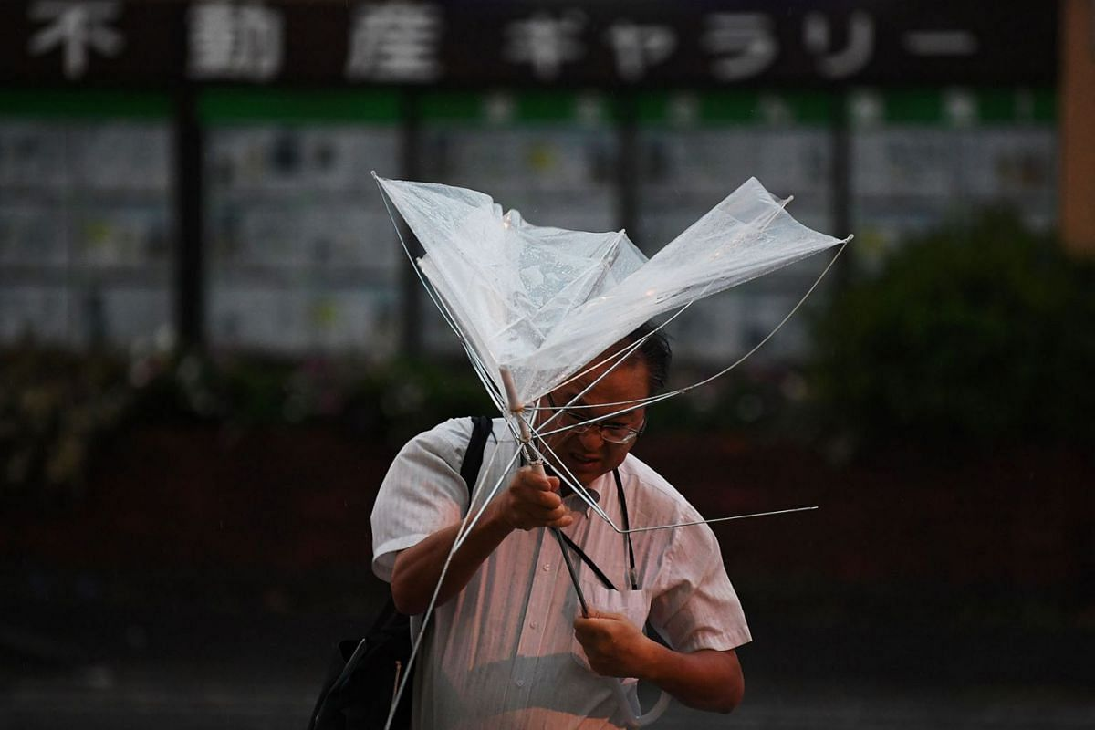 A man with an umbrella crosses a street early morning under the rain as a typhoon hits Tokyo on September 9, 2019. PHOTO: AFP