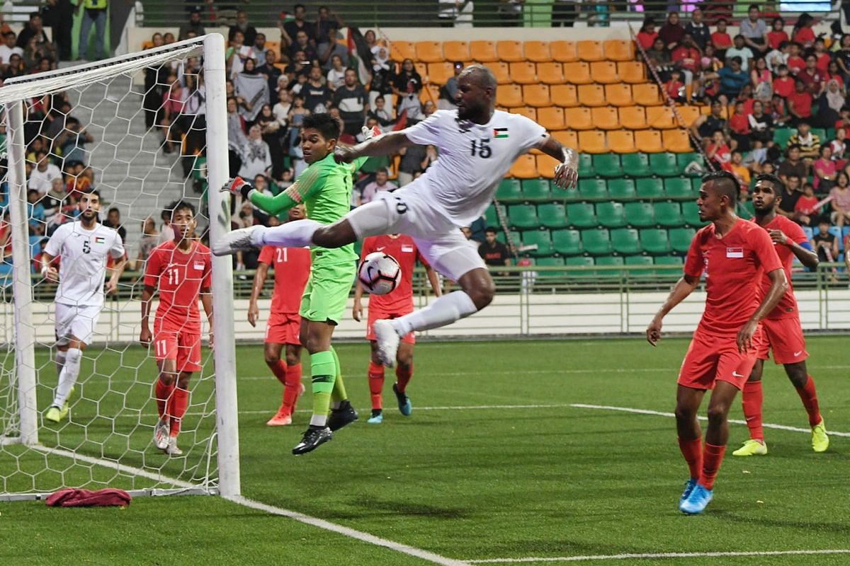 Singapore goalkeeper Izwan Mahbud marshalling his defence well as Palestine captain Abdellatif Bahdari fails to get the ball into the net at the Jalan Besar Stadium, September 10, 2019. Singapore defeated Palestine, 2 to 1 in the 2022 World Cup quali