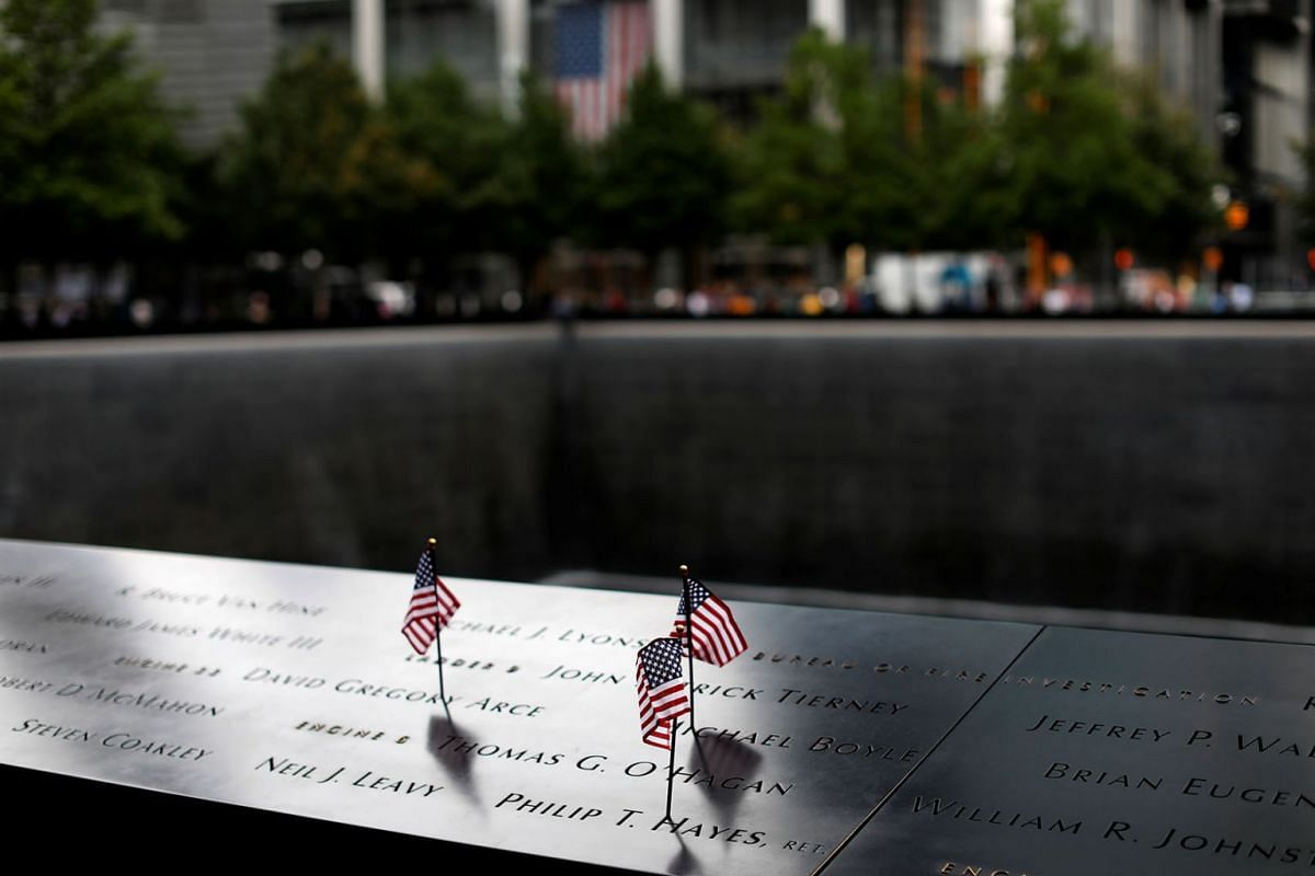American flags are seen left at the edge of the south reflecting pool at the 911 Memorial and Museum one day ahead of the United States' commemoration of the 18th anniversary of the September 11, 2001 attacks in New York, September 10, 2019. PHOTO: R