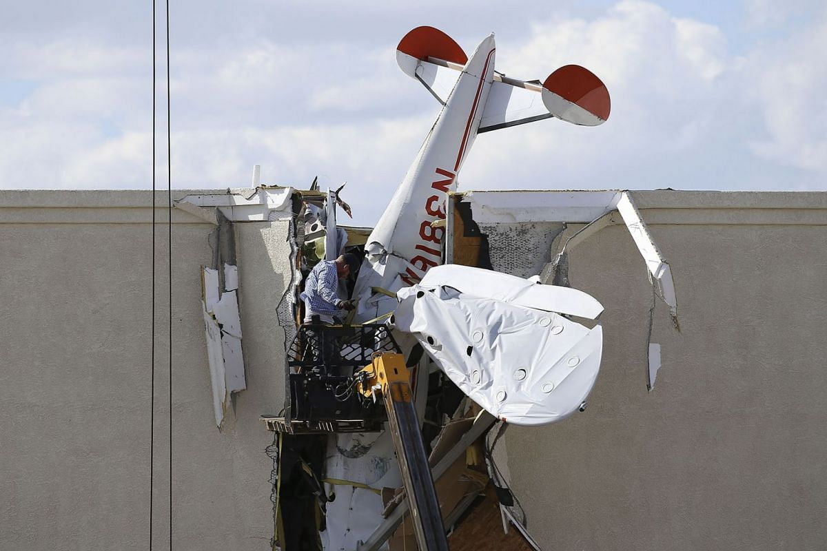 A worker pulls debris off a single engine plane prior to removal after it crashed into the terminal building shortly after takeoff at the Ak-Chin Regional Airport Tuesday, Sept. 10, 2019, in Maricopa, Ariz. The two people onboard suffered non-life-th
