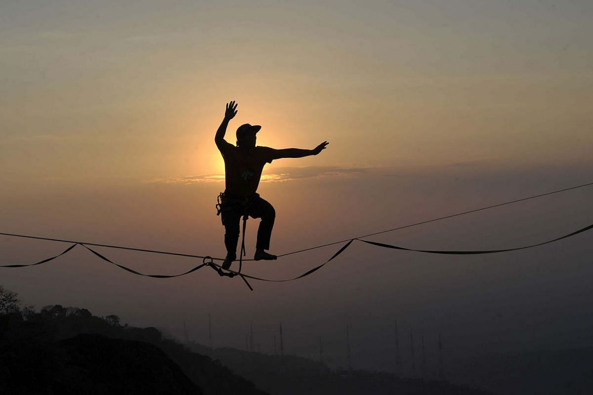 This picture taken on September 9, 2019 shows extreme sport athlete Andi Ardi walking on a tightrope at the height of 740 meters (2,427 ft.) on Mount Nglanggeran in Yogyakarta. PHOTO: AFP
