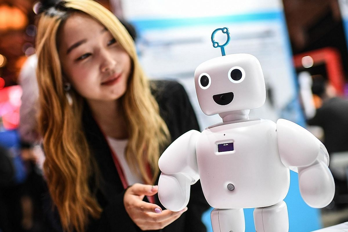 A visitor interacting with Pibo the robot at the IFA technology trade fair in Berlin, Germany, last week.