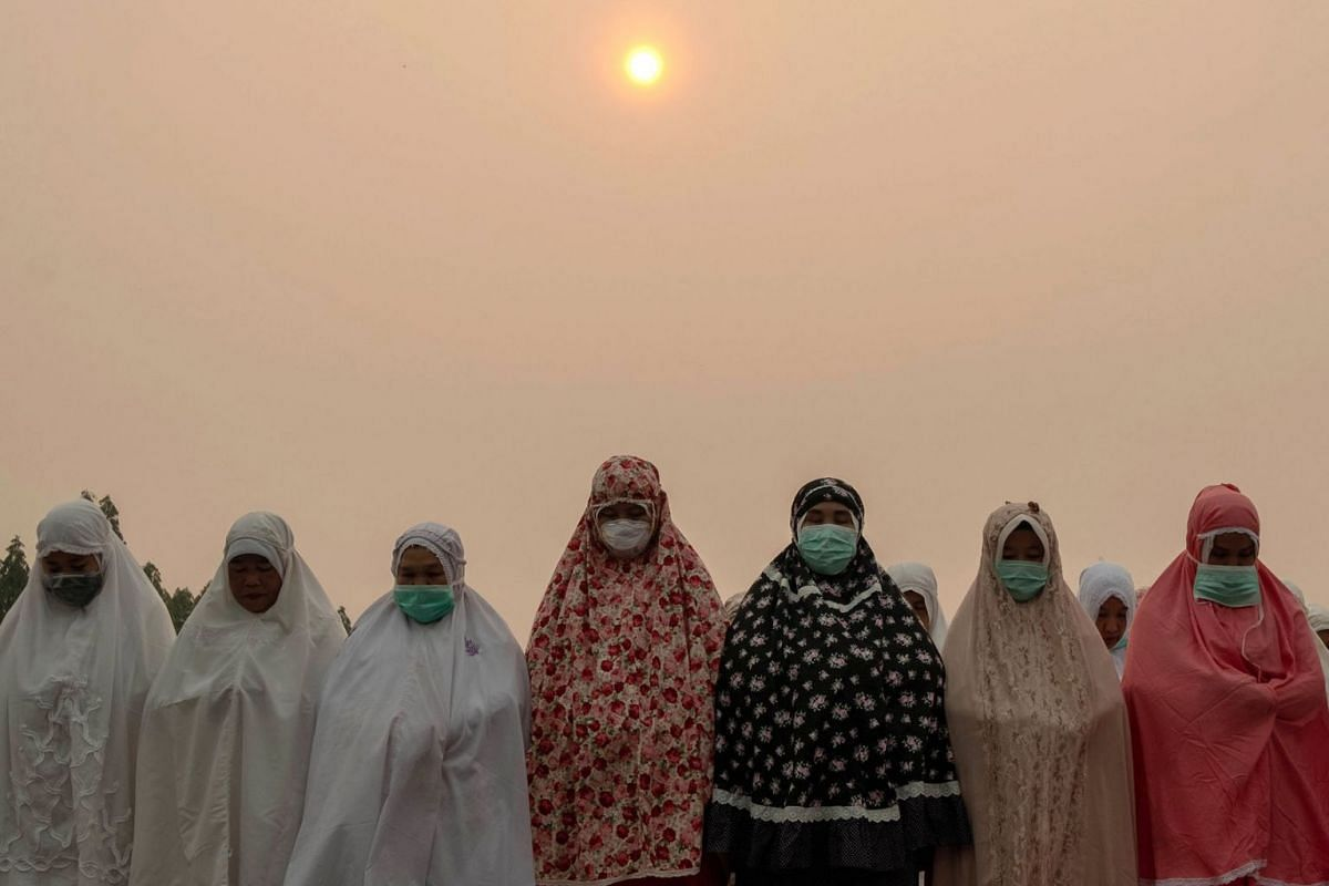 Indonesian Muslims wear protective masks as they perform a mass prayer for rain to combat the haze and drought season in Pekanbaru, Riau province, Indonesia, September 11, 2019. PHOTO: EPA-EFE