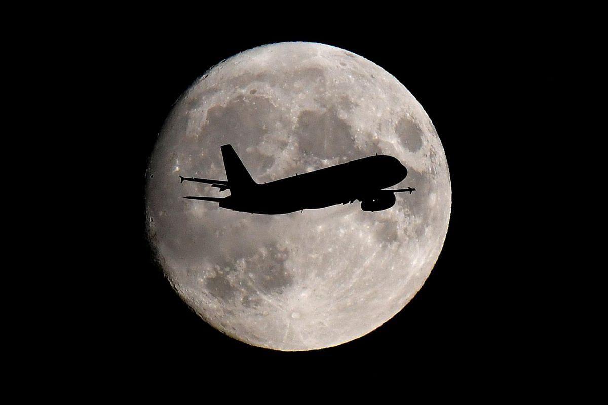 A passenger plane passes in front of the moon as it makes its final landing approach to Heathrow Airport in London, Britain, on Sept 12, 2019.