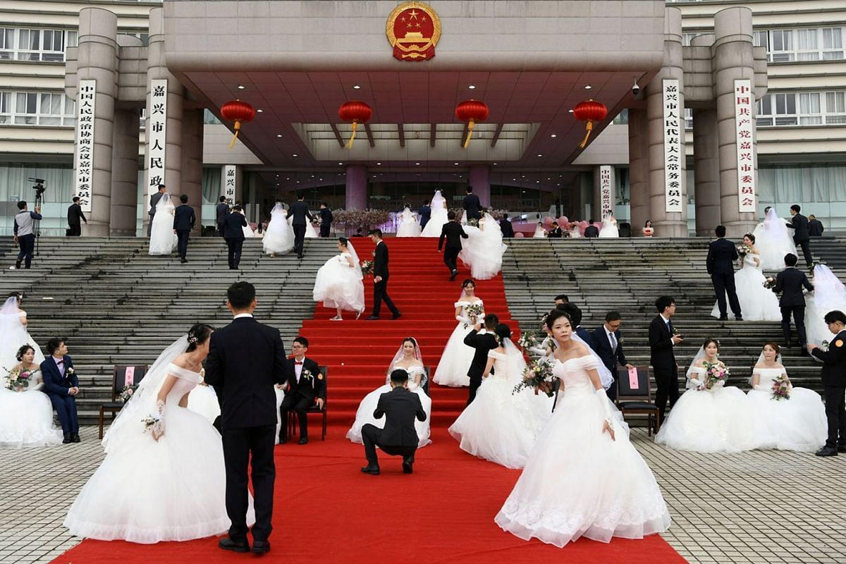 Couples attend a mass wedding at the city's municipal government building ahead of the 70th founding anniversary of People's Republic of China in Jiaxing, Zhejiang province, China, September 22, 2019.