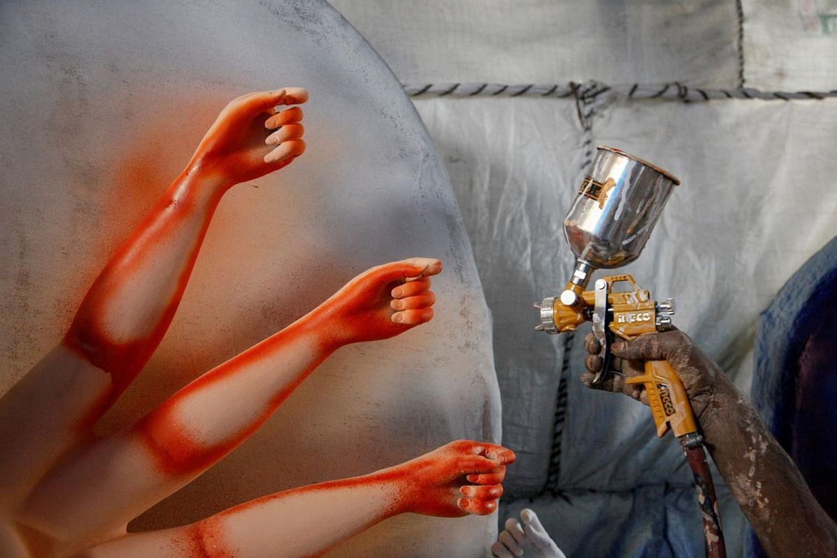 The hand of an artist is pictured as he sprays colour on an idol of Goddess Durga before selling it to a customer ahead of Dashain, a religious festival for Hindus in Lalitpur, Nepal, September 22, 2019.