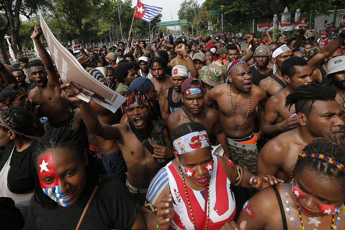 Papuan students and others from the province rallying near Indonesia's presidential palace in Jakarta on Aug 28 in a protest against racism and for independence for their region. Buildings on fire after hundreds of demonstrators marched near Papua's