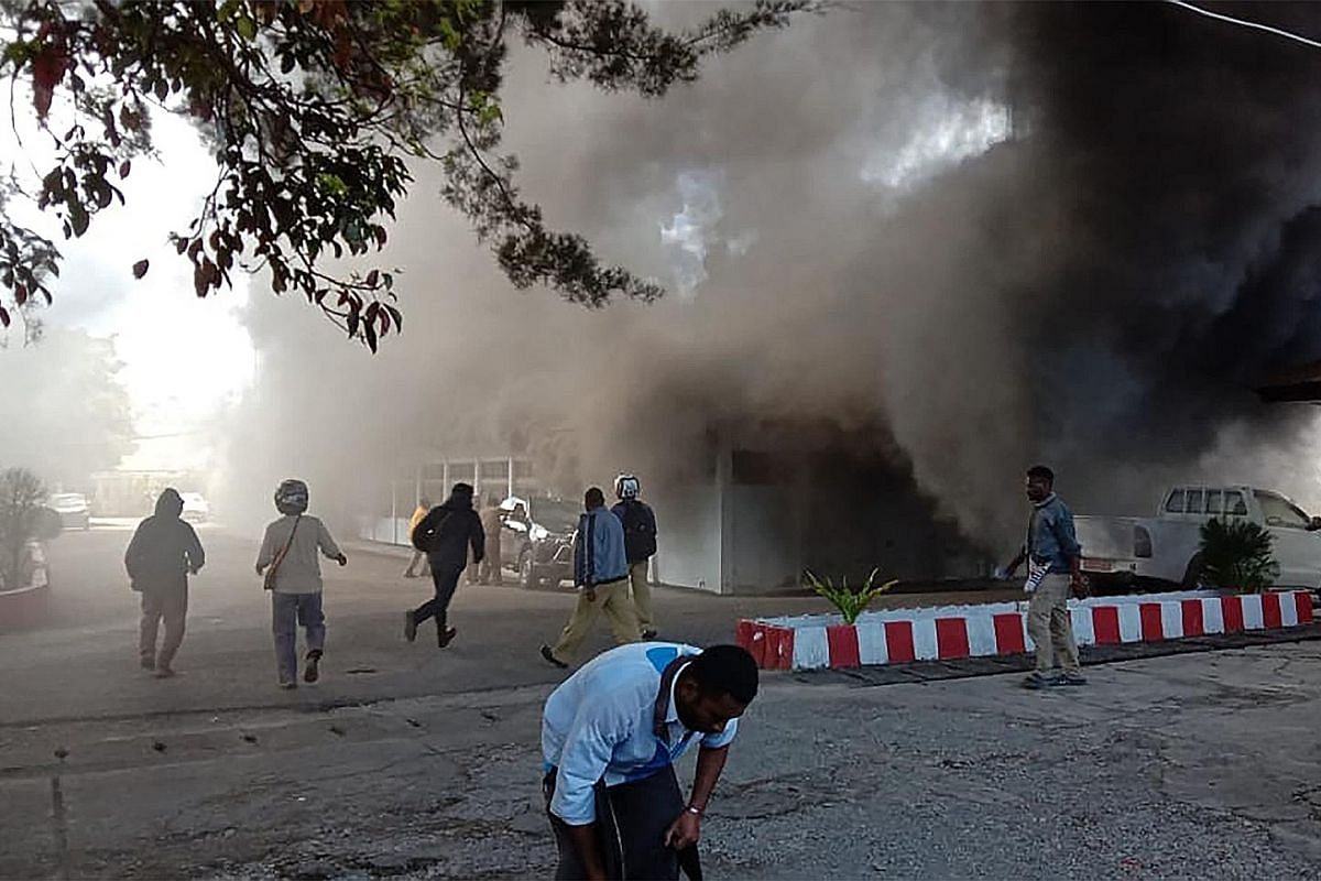 A building in flames after fresh protests broke out in Wamena, in Indonesia's restive province of Papua, yesterday. Indonesian riot police taking up positions at a university in Papua's provincial capital Jayapura yesterday as unrest erupted again fo