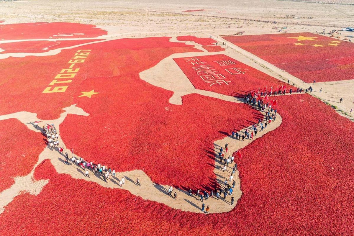 People walking amongst an image of a Chinese map and a national flag formed by dried chili peppers during the harvest season in Zhangye in China's northwestern Gansu province, as farmers celebrate the 70th anniversary of the founding of the People's