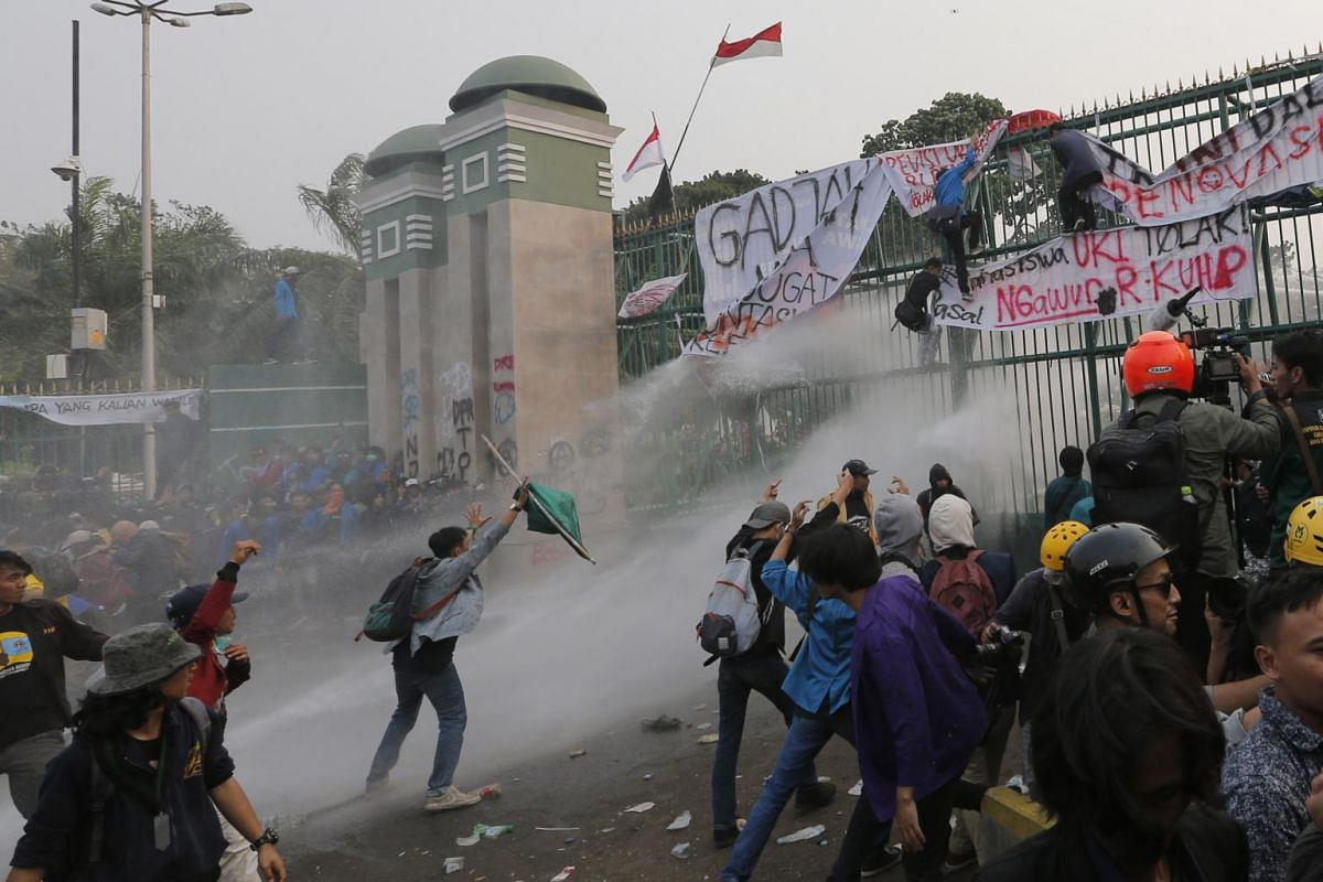 Student protesters are sprayed with water from a police water-cannon truck during a protest outside parliament in Jakarta, Indonesia, on Sept 24, 2019.
