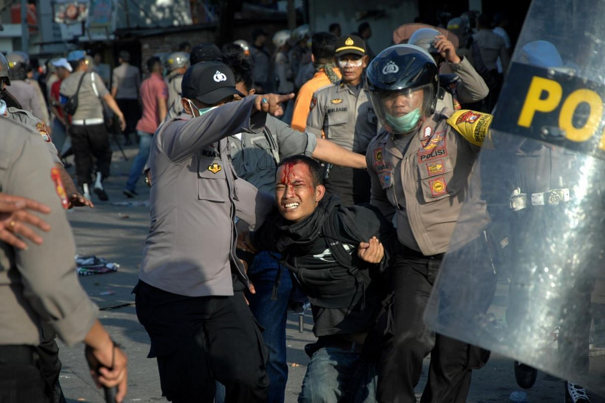 Police officers detain a protester during university students' protest outside the local parliament building in Makassar, South Sulawesi province, Indonesia on Sept 24, 2019.