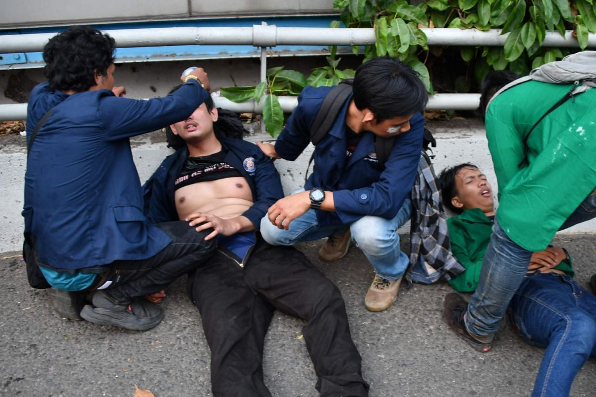 Students tend their injured friends during a protest against the government's proposed change in its criminal code laws and plans to weaken the anti-corruption commission, outside the parliament building in Jakarta on Sept 24, 2019.