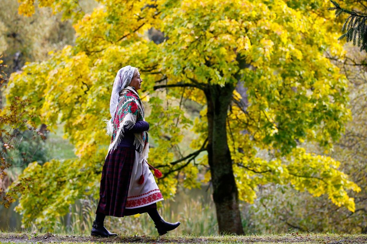A woman walks as she takes part in the autumn festival of traditional culture Bagach, which marks the end of the harvest, at the Yanka Kupala State Literary Museum near the village of Vyazynka, Belarus on Sept 29, 2019.