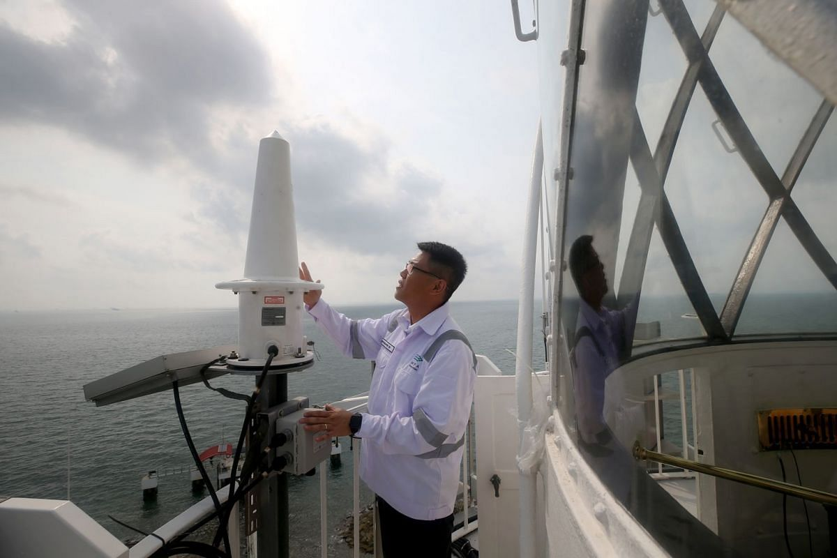 Mr Aw checks a solar-powered radar beacon at Raffles Lighthouse. The beacon sends a morse code transmission which is picked up by ships' radars, letting mariners know the lighthouse's location.