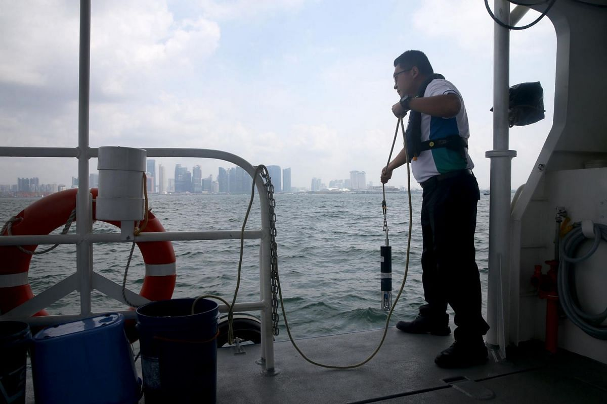 Mr Huang lowers a sound velocity profiler, which is used in hydrographic surveys, into the sea.