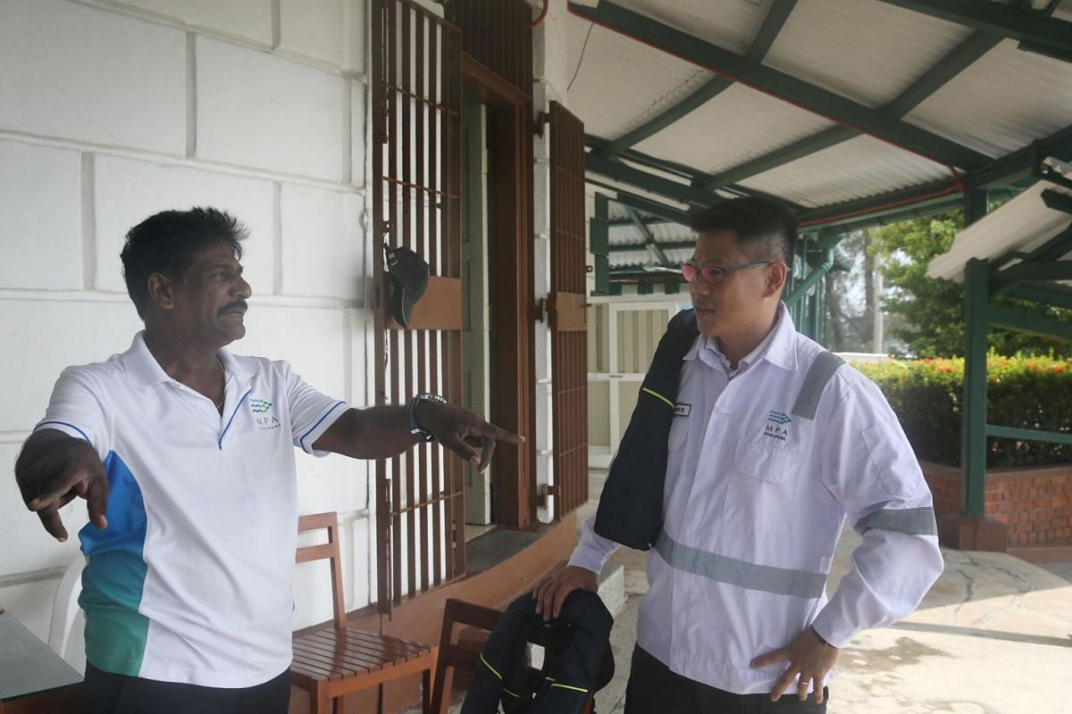 Mr Aw conversing with lighthouse keeper Mr V. Uthrapathi, 56, at Raffles Lighthouse.