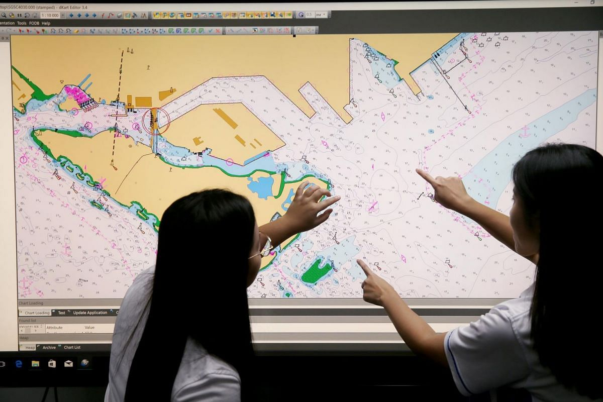 Ms Siti Nursyahirah Binte Sumsuri (left) and Ms Pearlyn Pang, Manager (GeoSpace-Sea), pore over an Electronic Navigational Chart.