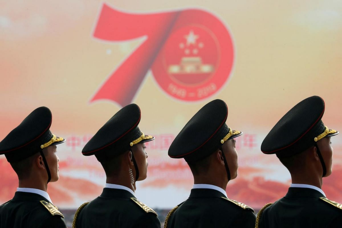 Soldiers in front of a sign marking the 70th founding anniversary of People's Republic of China before the military parade at Tiananmen Square.