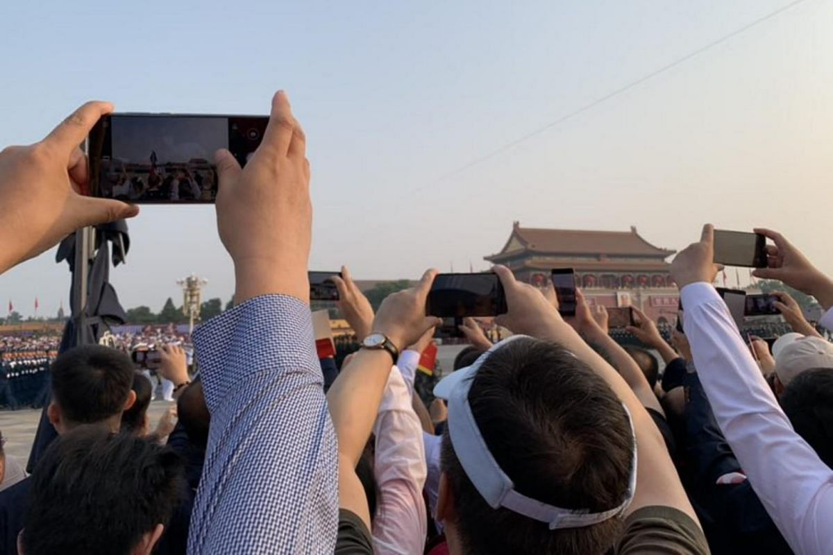 A crowd trying to snap a photo of a march past before the military parade at Tiananmen Square.