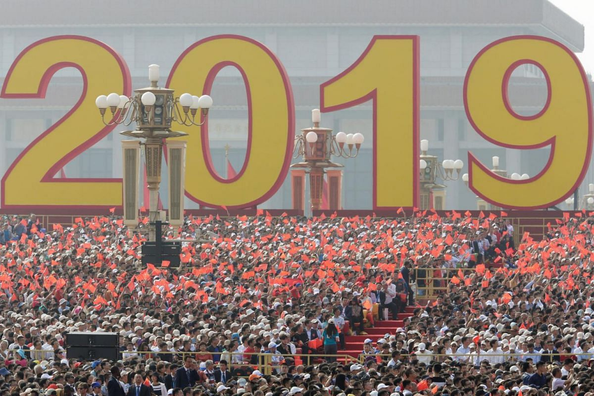 People wave Chinese flags before a military parade that is part of China's 70th anniversary celebrations at Tiananmen Square.