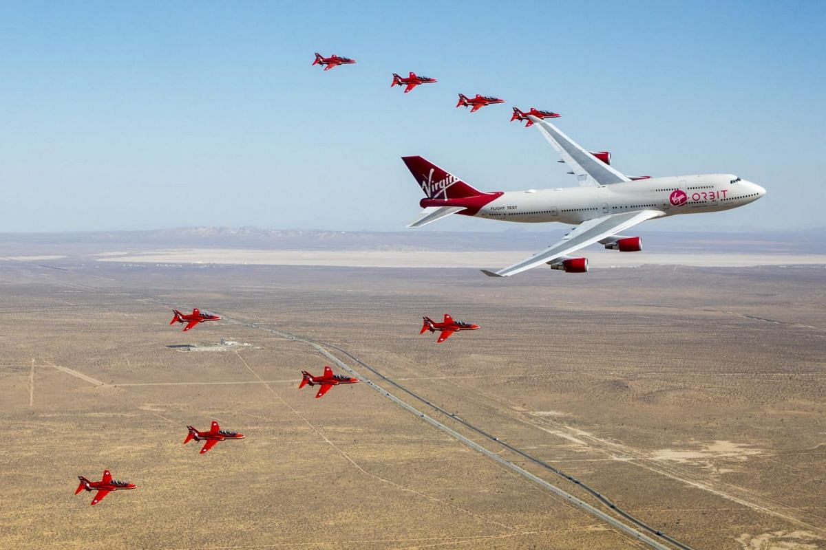 A handout picture provided by the British Ministry of Defence shows Virgin Orbit 'Cosmic Girl' launch aircraft flying in formation alongside the Red Arrows Hawk jets in Long Beach, California, on Oct 2, 2019.