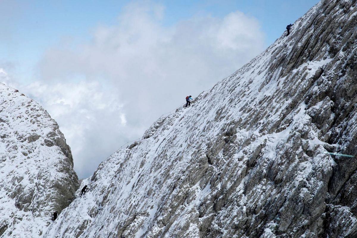 Hikers walk through freshly fallen snow on a ridge near the peak of the north-eastern Swiss landmark Mount Saentis, Switzerland, on Oct 3, 2019.