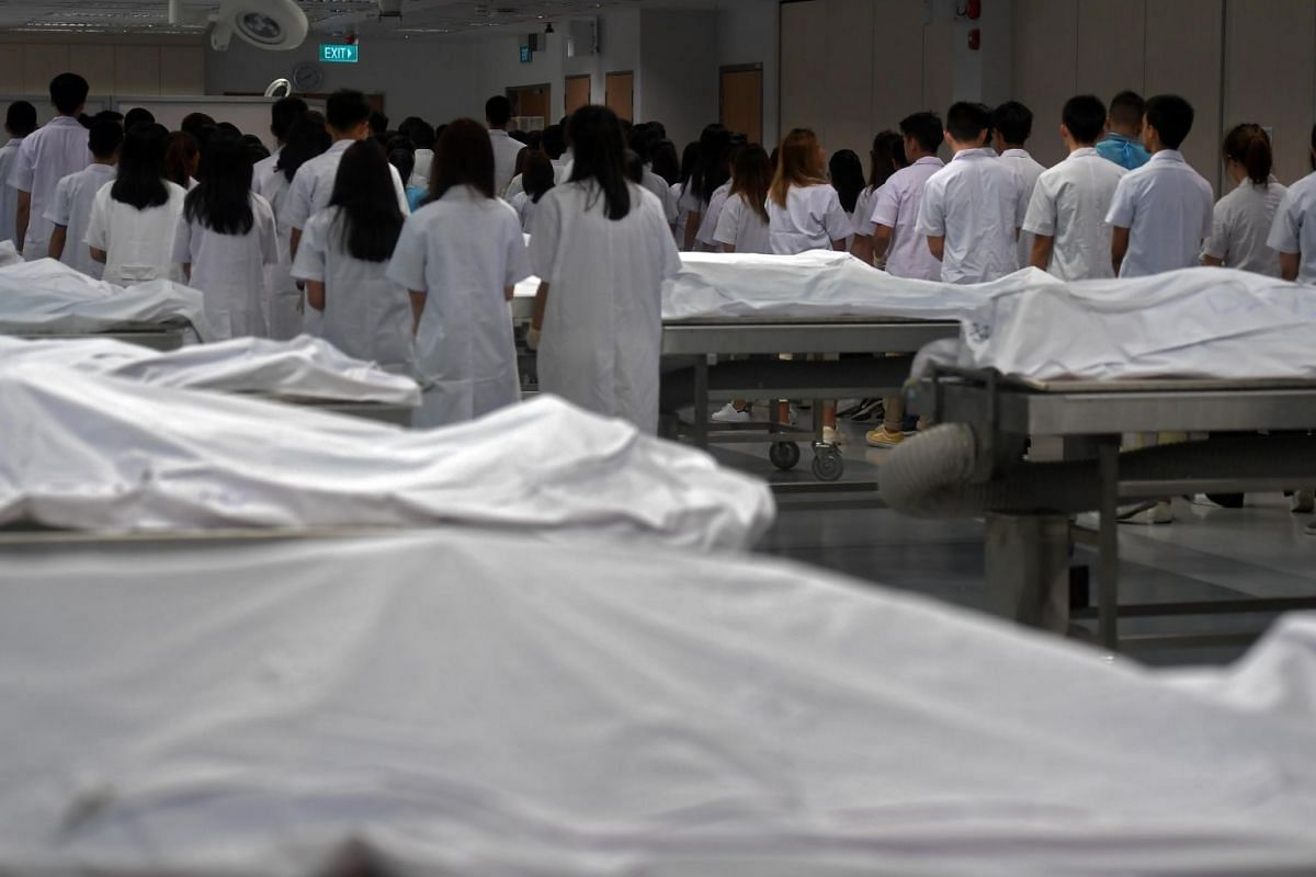 First-year medical students leaving the anatomy hall after reciting the Anatomy Student's Oath on Aug 16, 2019. They were asked to unzip the bags, place their left hands on the cadavers and raise their right hands to take a pledge to treat them wit