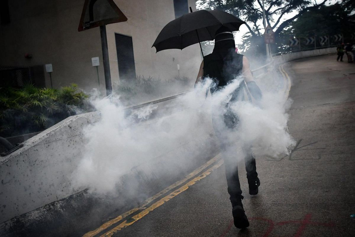 A protester picks up a tear gas canister and runs towards the police to throw it back at them in Wan Chai, Hong Kong, on Oct 6, 2019.
