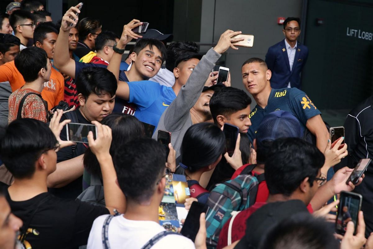 Brazil forward Richarlison takes photos with fans as he departs JW Marriott Singapore South Beach for an evening training session on Oct 7, 2019. About 40 fans were present to catch a glimpse of their football idols.