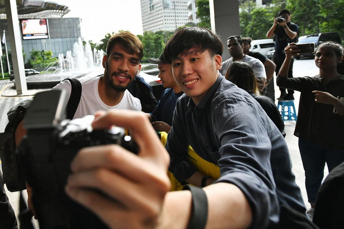 Brazil team player Lucas Paqueta takes a photograph with a fan at the JW Marriott Hotel Singapore South Beach on Oct 7, 2019.