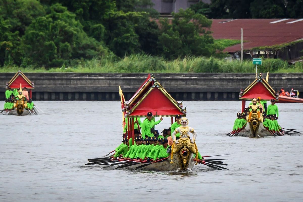 Royal Thai Navy personnel rowing vessels during a rehearsal for the royal barge procession along the Chao Phraya.