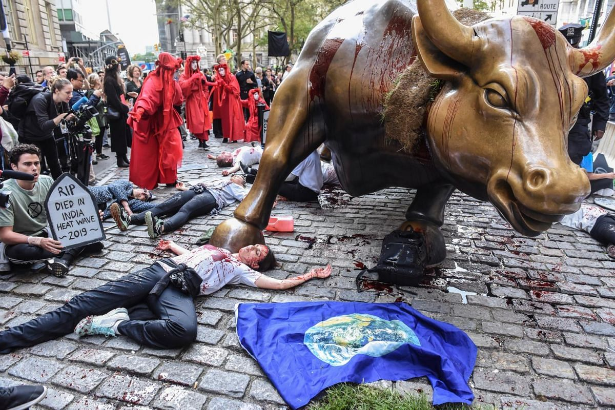Demonstrators lay motionless, to represent deaths from climate-related disease and disaster, near the Charging Bull statue in New York, on Oct 7, 2019.