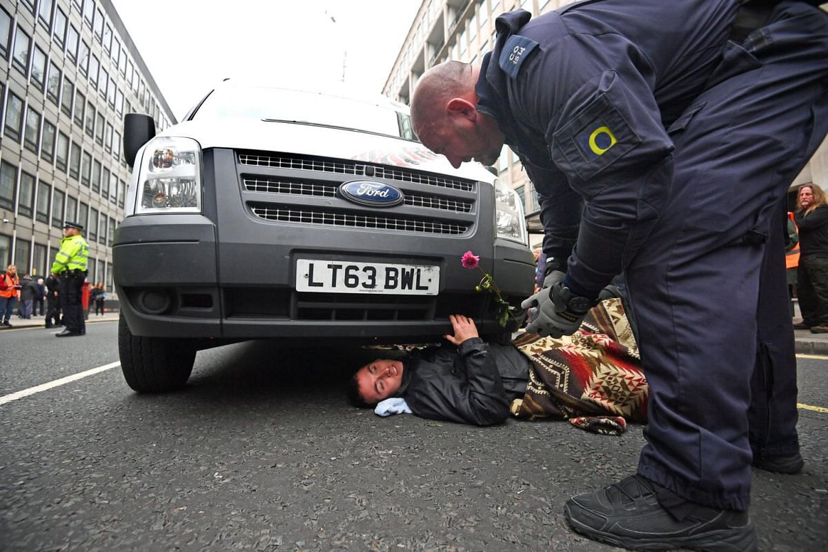 Protester lays beneath a vehicle which blocks Victoria Street during an Extinction Rebellion protest, outside the government Department of Business, Energy and Industrial Strategy.
