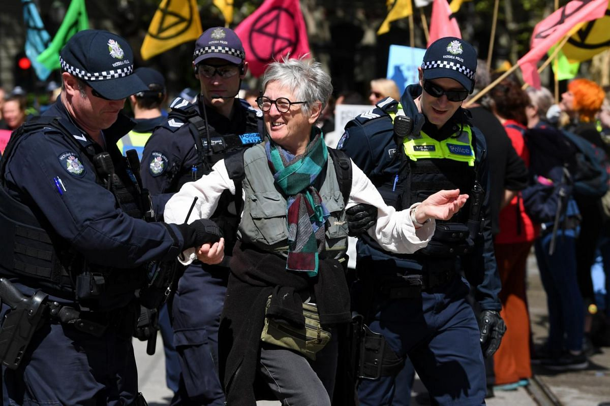 Policemen arrest an activist during a protest held by activists of environmental movement Extinction Rebellion held to draw attention to climate change.