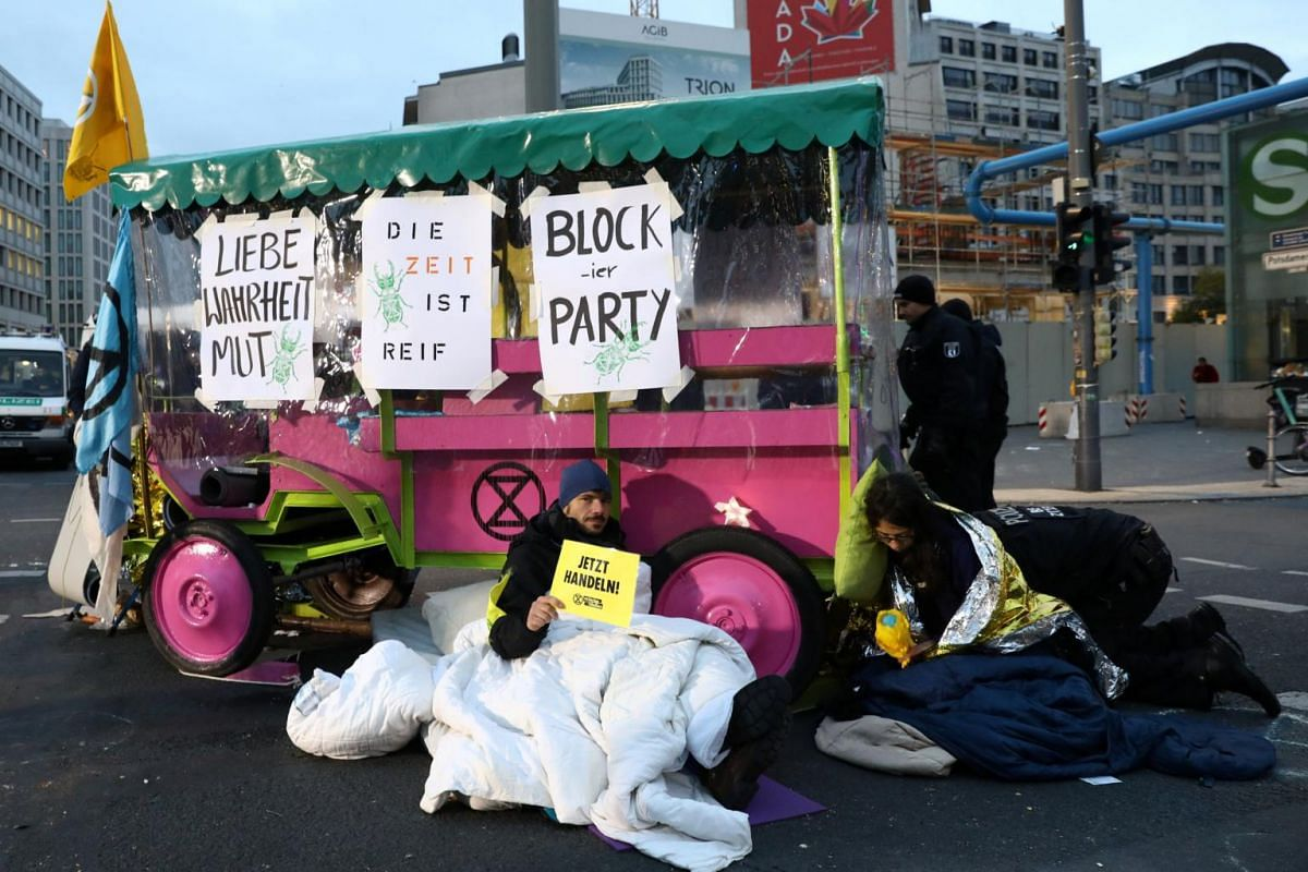 """Demonstrators from Extinction Rebellion block a street during the launch of a new wave of """"civil disobedience"""" at Potsdamer Platz in Berlin, Germany, on Oct 8, 2019."""