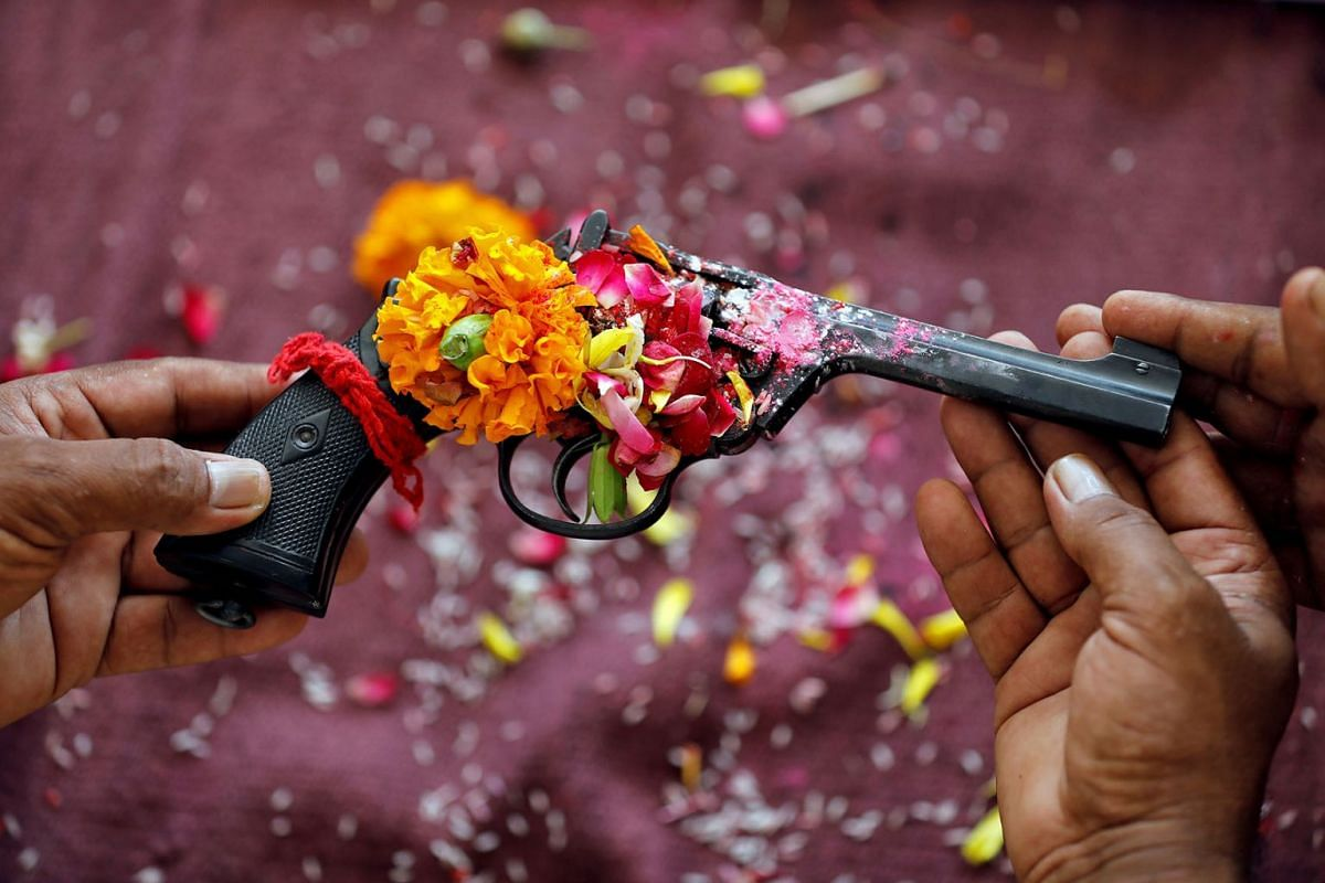 Police officers hold a revolver as they offer prayers to their weapons as part of a ritual at their headquarters on the occasion of Dussehra, or Vijaya Dashami, festival in Ahmedabad, India, October 8, 2019. PHOTO: REUTERS