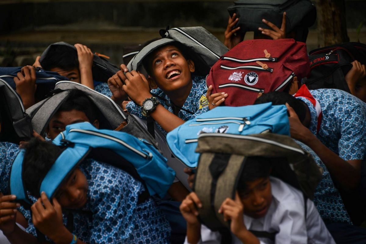 Students cover their heads during an earthquake and tsunami drill at their school in Banda Aceh on October 9, 2018. PHOTO: AFP