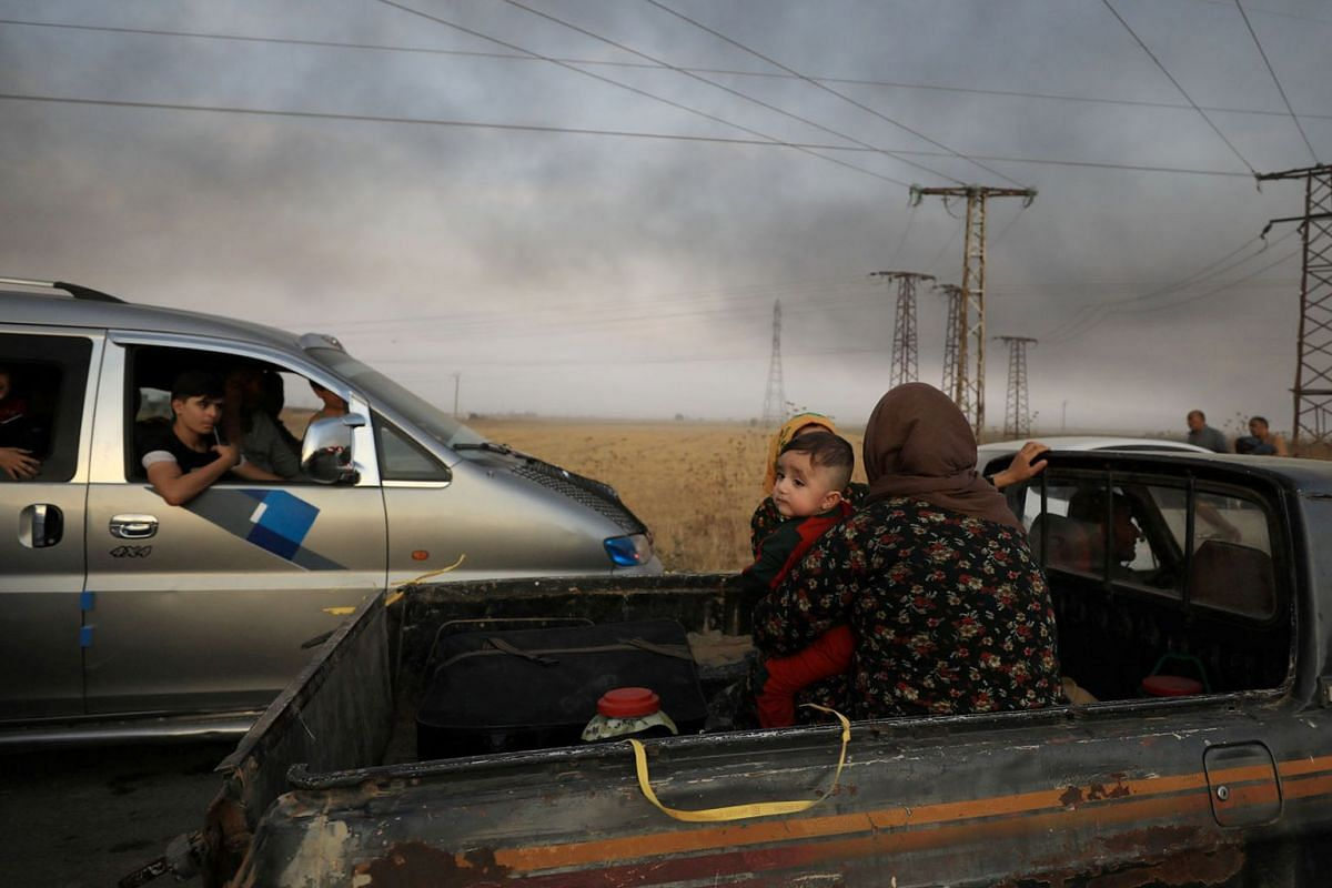 A woman with a baby sits at a back of a truck as they flee Ras al Ain town, Syria October 9, 2019. PHOTO: REUTERS