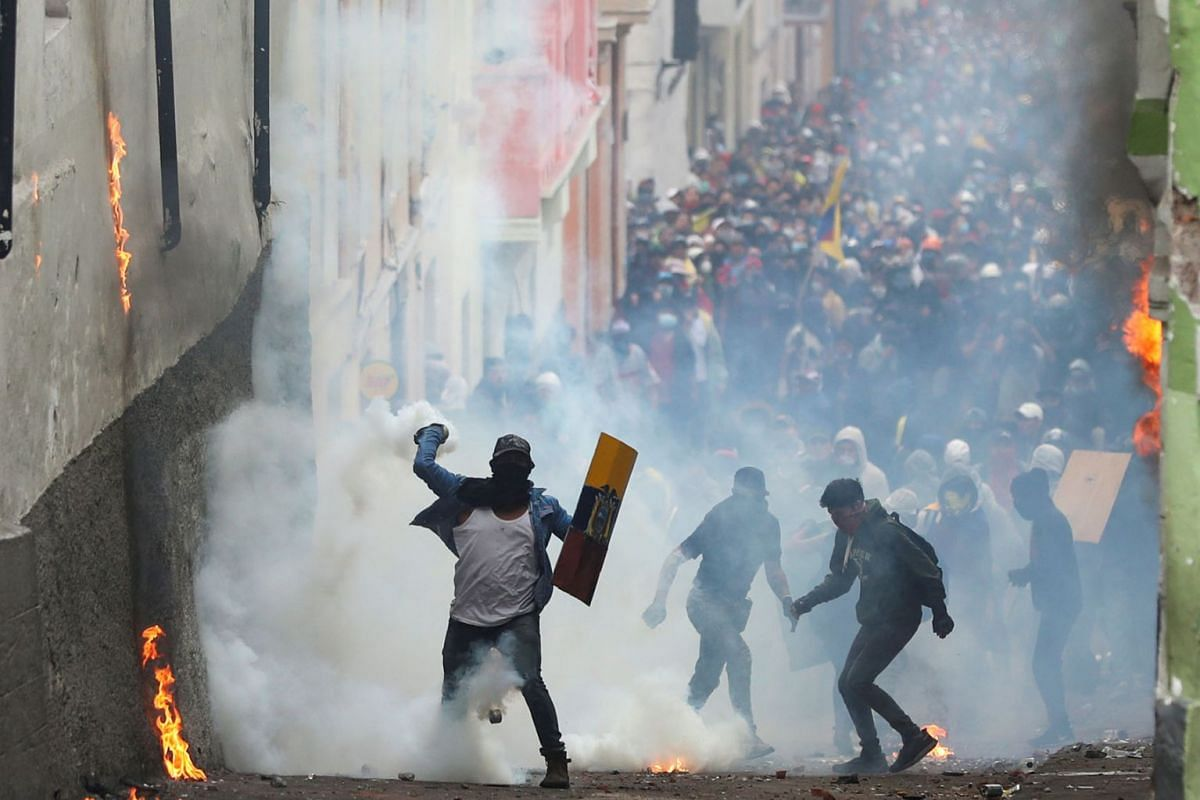 A demonstrator throws back a tear gas canister during a protest against Ecuador's President Lenin Moreno's austerity measures in Quito, Ecuador, October 9, 2019. PHOTO: REUTERS