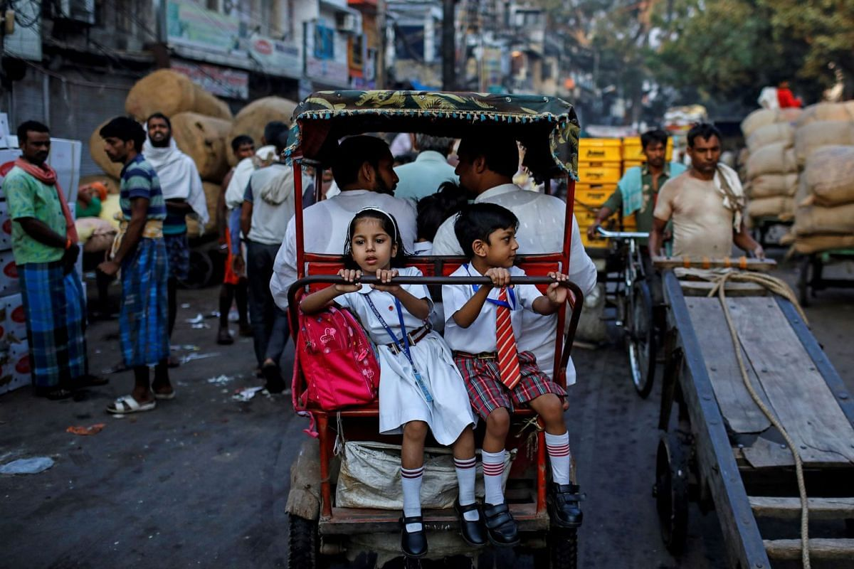 School children ride in a cycle rickshaw through a market in the old quarters of Delhi, India, October 10, 2019. PHOTO: REUTERS