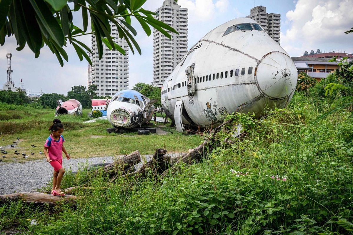 """A child plays in front of abandoned aircraft in the suburbs of Bangkok on October 9, 2019.  The area, known as the """"airplane graveyard"""", has become a tourist attraction in the Thai capital. PHOTO: AFP"""