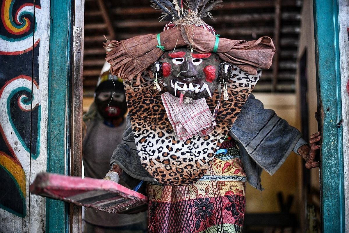 Tourists joining in a traditional Dayak dance, in which huge sticks are used. A performer in traditional clothes. At Pampang Cultural Village, tourists watch cultural performances and shop for Dayak handicrafts. Law graduate Novianti Liq, 24, about t