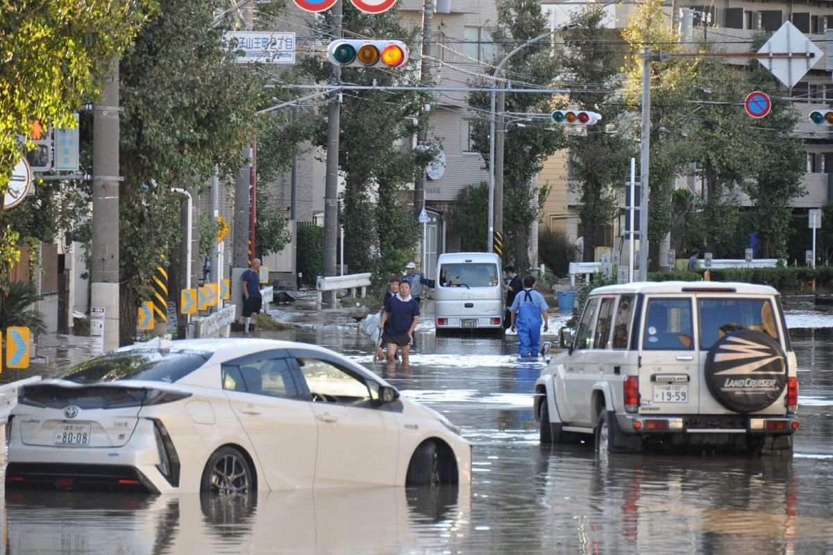 Residents walking on a flooded street in the aftermath of Typhoon Hagibis in Kawasaki, on Oct 13, 2019.