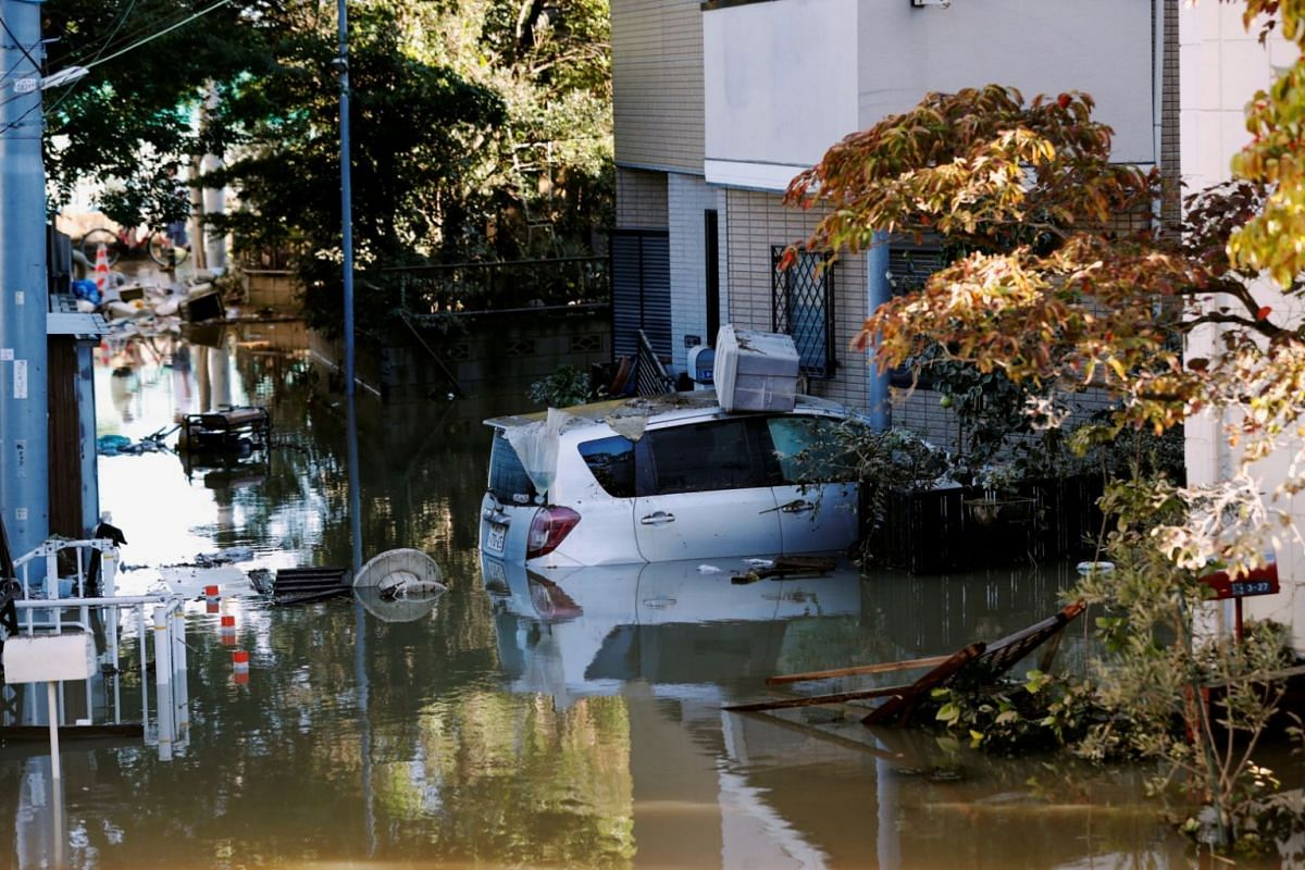 A car is seen partially submerged in a flooded residential area near the Tama River in Kawasaki, on Oct 13, 2019.